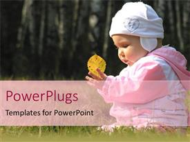 PowerPoint template displaying baby girl in hat and coat holding yellow leaf in grass