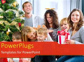PowerPlugs: PowerPoint template with big happy family celebrating at christmas with gift box beside christmas tree