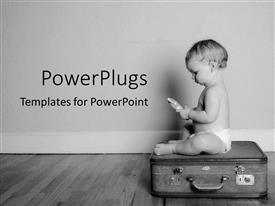 PowerPoint template displaying black and white representation of baby sitting on top of suitcase holding toy in hands