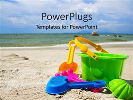 PowerPlugs: PowerPoint template with a bucket and spades on the beach with the sea in the background