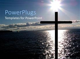 PowerPlugs: PowerPoint template with cross silhouette in front of sea water and sun reflected on the water