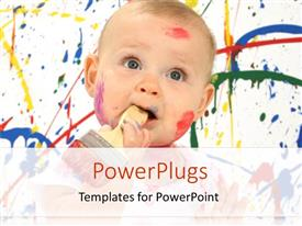 PowerPoint template displaying cute baby playing with colors and paint brush in mouth