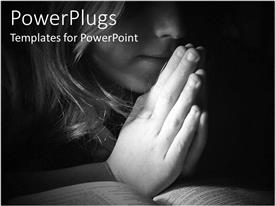 PowerPoint template displaying girl praying with a bible on a black and white background