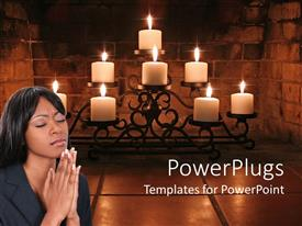 PowerPoint template displaying a girl praying with burning candles in the background
