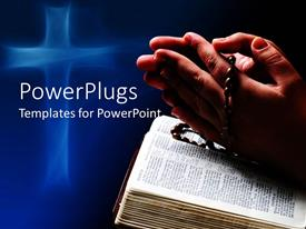 PowerPoint template displaying hands in prayer holding religious bracelet on open Bible book with abstract glowing cross on blue background