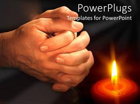 PowerPoint template displaying man hands praying near burning candle light on black background