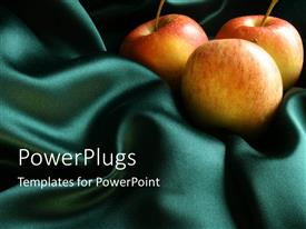 PowerPoint template displaying three red apples on a green silk cloth material