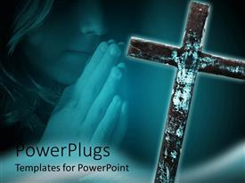 PowerPlugs: PowerPoint template with wooden cross on  a blue background with a girl praying
